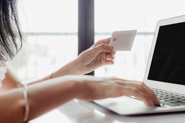 Woman's hand holding a credit card and using computer for online shopping and payment concept