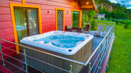 Hot tub with water on the terrace of the wooden house. Cottage v