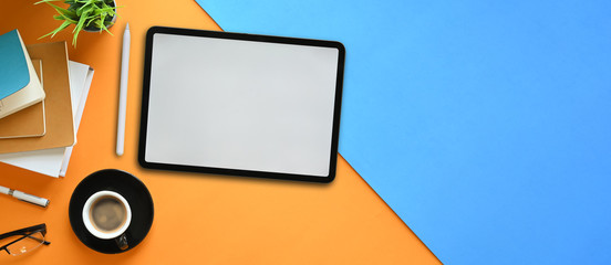 Top view image of white blank screen computer tablet with stylus pen putting on two tones colorful...