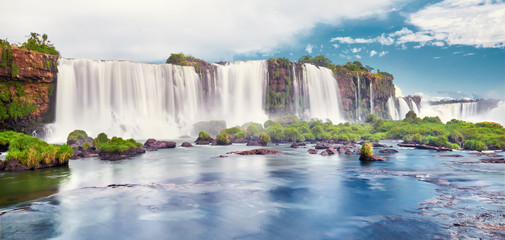 Foto auf Leinwand Wasserfalle Iguazu waterfalls in Argentina, view from Devil's Mouth. Panoramic view of many majestic powerful water cascades with mist and clouds. Panoramic image of Iguazu valley with stones in water.