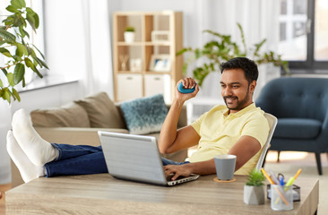 technology, remote job and lifestyle concept - happy smiling indian man with laptop computer gripping hand expander and resting feet on table at home office