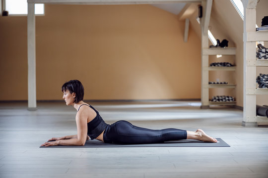 Side view of fit attractive yogi woman with brown hair in Sphinx yoga pose. Yoga studio interior.