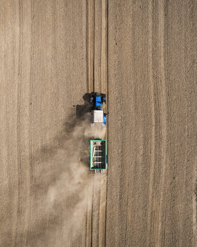 Aerial view of a blue tractor working in a field with a fertilizer and seed spreader