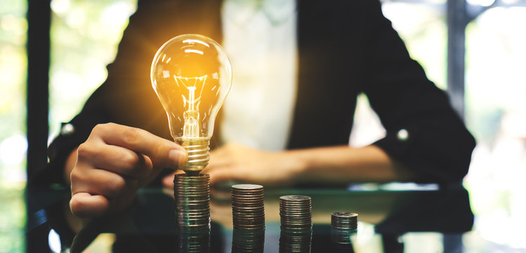 Businesswoman putting lightbulb over coins stack on table for saving energy and money concept
