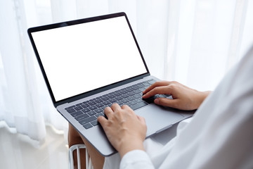 Mockup image of a woman working and typing on laptop computer with blank screen while sitting in a...