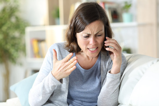 Angry middle age woman arguing calling on phone at home