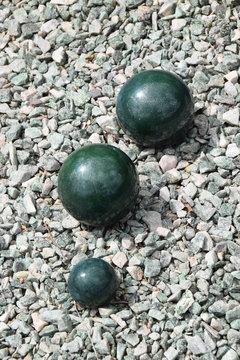 Grüne Steinkugeln als Grabdekoration