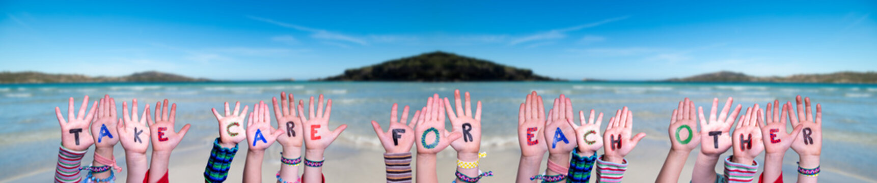 Children Hands Building Colorful English Word Take Care For Each Other. Ocean And Beach As Background