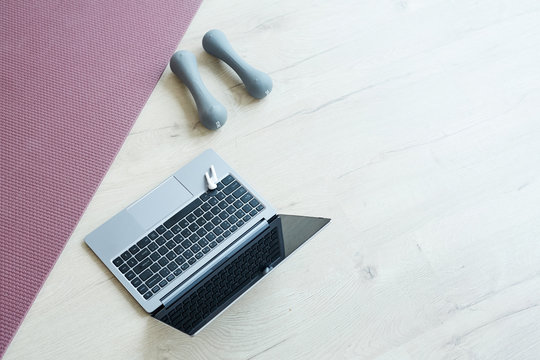 Minimal background image of yoga mat and dumbbells by computer laptop on wooden floor, online workout at home concept, copy space