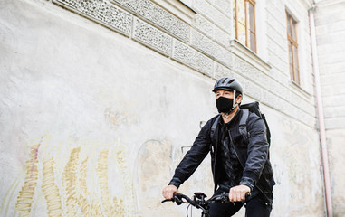 Delivery man courier with face mask and bicycle cycling in town.