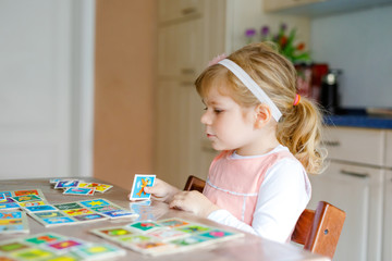 Adorable cute toddler girl playing picture card game. Happy healthy child training memory, thinking. Creative indoors leisure and education of kid during pandemic coronavirus covid quarantine disease Wall mural