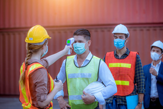 Woman worker used a medical Digital  temperature Thermometer to check staff body temperature before start work in factory ,they wearing face mask the concept of a corona virus [Covid-19] screening.