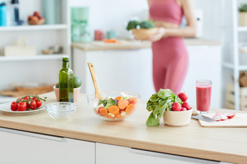 Close up of healthy food ingredients and salad bowl on kitchen counter with blurred shape of fit young woman in background, copy space