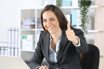 Happy executive gesturing thumbs up at office