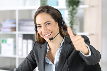 Happy telemarketer with thumbs up looking camera at office