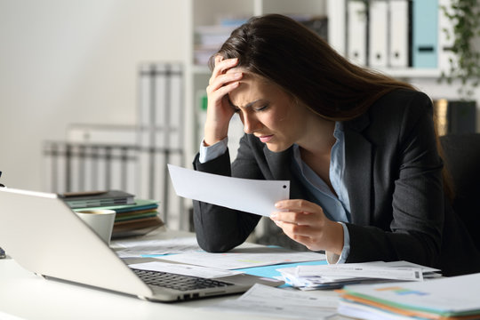 Sad executive complaining holding receipt at night at office