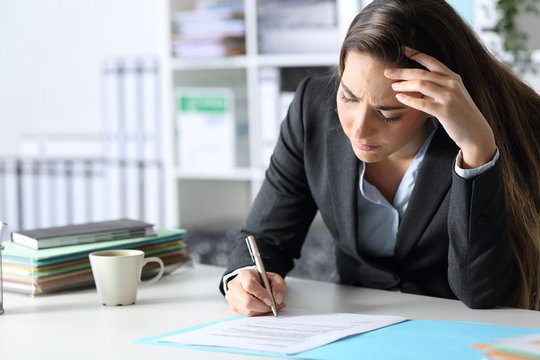 Worried executive signing contract sitting at office