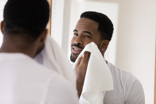 Handsome young african American man look in mirror in bathroom wipe rub face with towel after shower, millennial biracial male do morning beauty procedures, wash in bath, hygiene, skincare concept