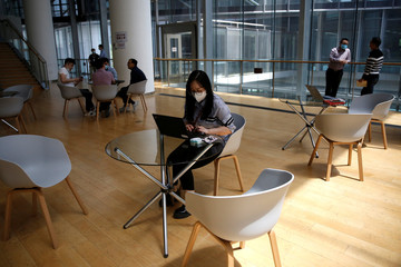 Employee wearing a face mask uses a laptop at Baidu's headquarters in Beijing