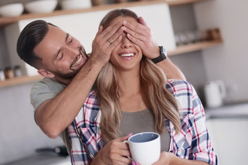 Spoed Fotobehang Hoogte schaal happy man joking with his girlfriend in the kitchen in the morning