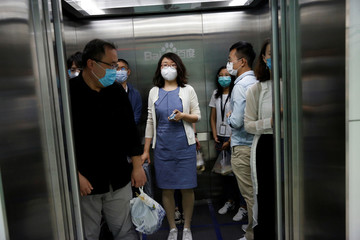 Employees wearing face masks are seen inside an elevator at Baidu's headquarters in Beijing