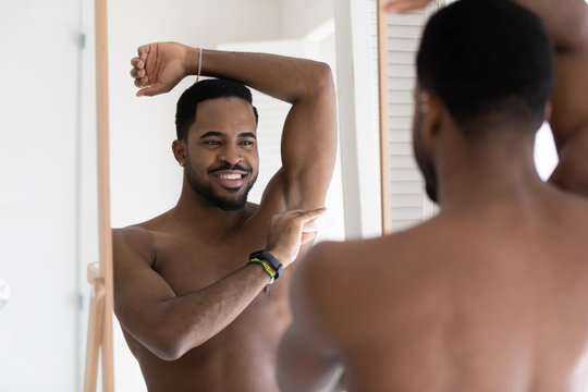 Smiling young naked african American man look in mirror in bathroom after shower apply deodorant on armpit, happy handsome millennial male use dry stick antiperspirant in bath, body hygiene concept