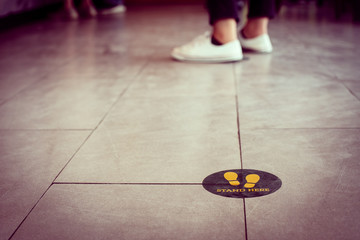 Stand here foot sign or symbol on the floor in coffee shop