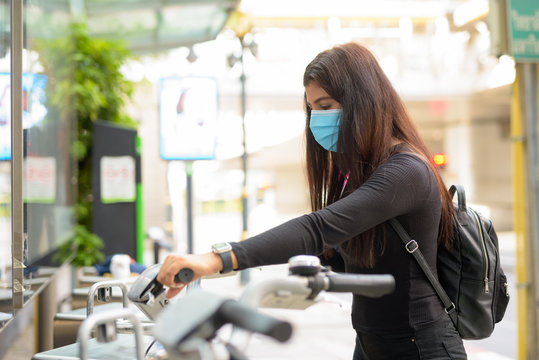 Profile view of young Indian woman with mask riding bike at public bicycle service station