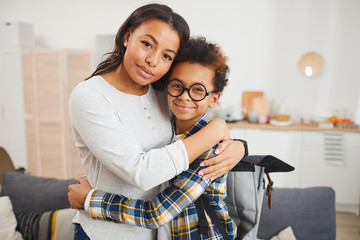 Waist up portrait of happy African-American mom embracing son while sending him to School in September, both looking at camera