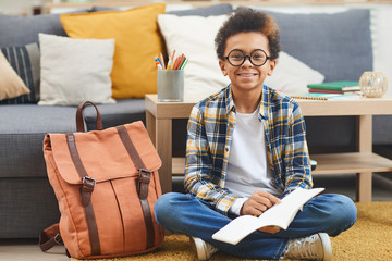 Full length portrait of cute African-American boy holding notebook and smiling at camera while sitting on floor at home, copy space