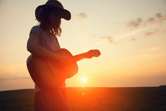 silhouette of young free woman in straw hat playing country music on a guitar at sunset, copy space