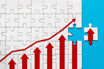White jigsaw puzzle and graph arrow growth up on blue background. Business growth success process...