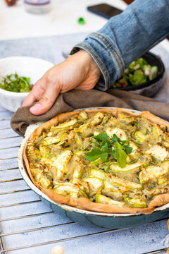 Vegetable casserole or tart with potato and zucchini. Vegan healthy food. Woman hands