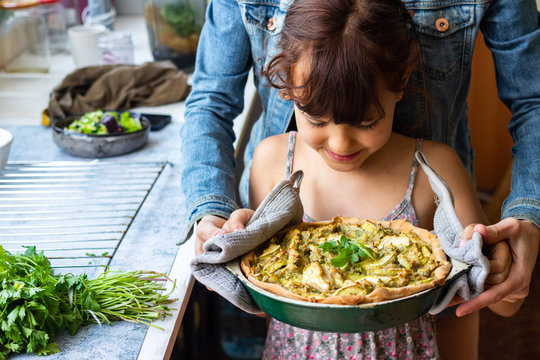 Mother and daughter hold vegan food together in hands. Vegetables casserole tart with potato, zucchini
