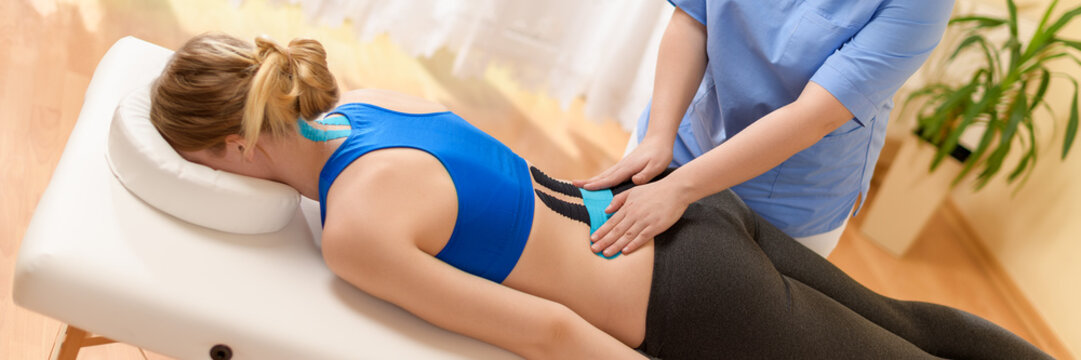 Physical therapist applying kinesio tape on female patient's lower back. Kinesiology, physical therapy, rehabilitation concept web banner.