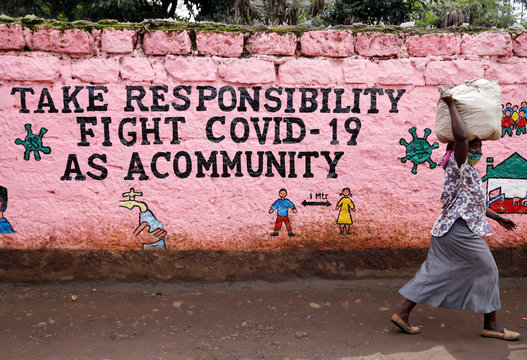A woman walks past a wall painted with a slogan calling for action against the coronavirus disease (COVID-19) in the Kibera slum of Nairobi