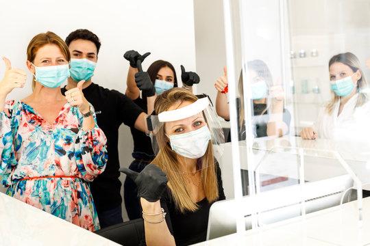 gruppo affiatato di lavoro con in primo piano la segretaria fornita di tutti i dispositivi di protezione e il resto della squadra con mascherina chirurgica
