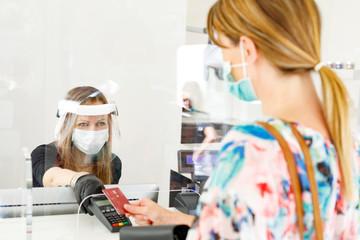 dentro un locale commerciale la cliente paga alla cassa con carta di credito munita di mascherina e...