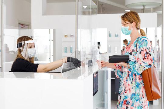 dentro un locale commerciale la cliente paga alla cassa con carta di credito munita di mascherina e separata dalla cassiera da un separatore di plexiglass