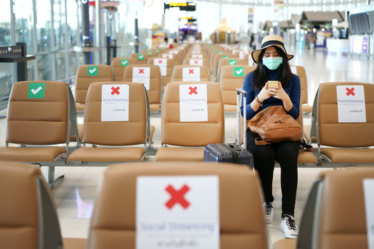 Young Asian traveler sitting at the international airport during COVID-19 disease crisis with social distancing and wearing mask. Playing mobile phone, waiting for airline counter check-in open.