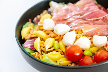 Salad made with cooked pasta, mixed green salads, cherry tomatoes, Mozzarella cheese and smoked ham served with accompaniment