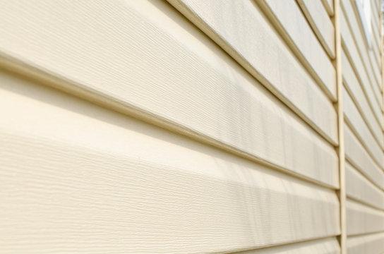 Light beige vinyl siding of the house. Plastic panels texture.