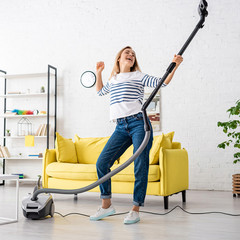 Blonde woman singing with closed eyes and vacuum cleaner near sofa in living room