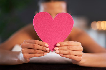 Relaxed woman waiting for a back massage and holding heart