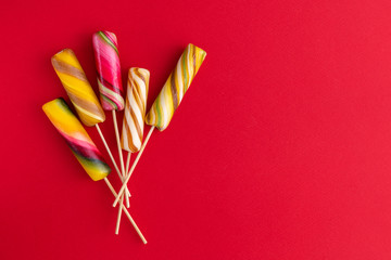 Sweet colorful lolly pops on red