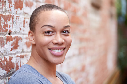 Outdoor Portrait Of Young Woman With Shaved Head Standing In The Street Leaning Against Wall