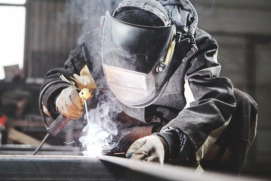 Welder working with welding on metal frames in an industrial plant.