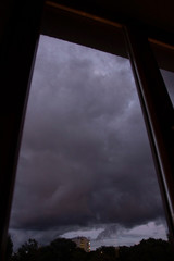 Very dark clouds outside of a window