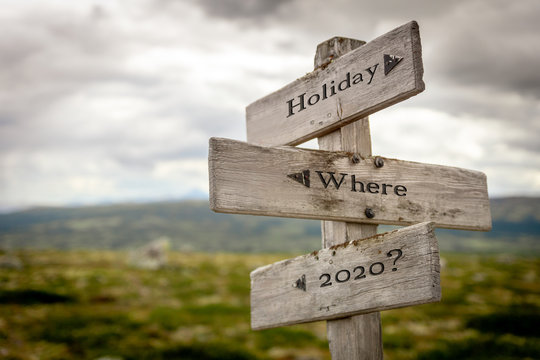 holiday where 2020 text engraved on wooden signpost outdoors in nature.