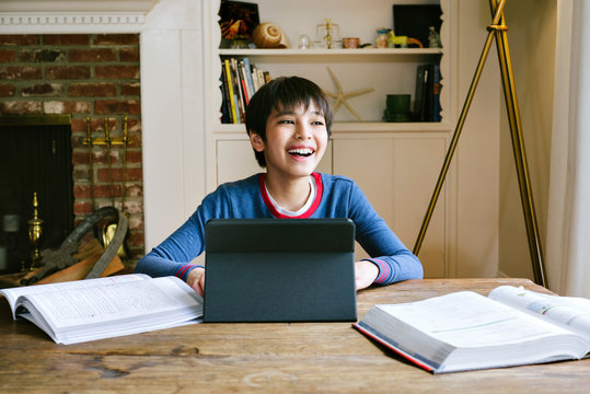 Male adolescent smiles off camera as he studies from home during quarantine - Covid 19 - Orders - School